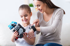 Positive mother and her daughter playing with robot stock photo