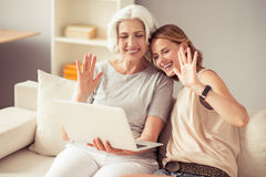 Positive mother and her daughter using laptop. Nice to see you. Positive content smiling aged women and her adult daughter sitting on the sofa and waving hands Royalty Free Stock Image