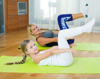 Positive mother and little daughter working out at home Stock Photo
