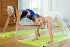 Positive mother and little daughter working out at home Royalty Free Stock Photography