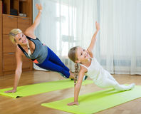 Positive mother and little daughter working out at home Royalty Free Stock Images
