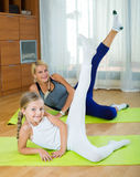 Positive mother and little daughter working out at home Stock Image