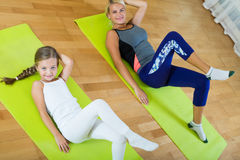Positive mother and little daughter working out at home Royalty Free Stock Image