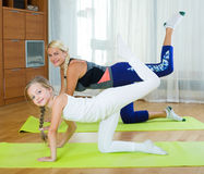 Positive mother and little daughter working out at home Stock Images