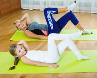 Positive mother and little daughter working out at home Royalty Free Stock Photo