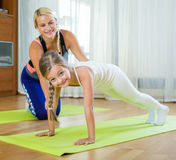 Positive mother and little daughter working out at home Stock Photography