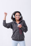 Positive mulatto woman listening to music. Involved in fun. Vivacious mulatto woman holding mobile phone and keeping the hand up while listening to music Royalty Free Stock Photos