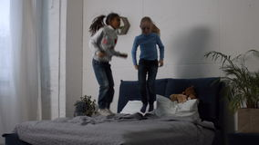 Positive multi ethnic kids jumping on the bed. Carefree preteen multiracial girls playing and having fun in bedroom. Cheerful little diversity girls jumping on stock footage