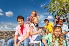 Positive multinational group of kids sit together. Positive multinational group of kids sitting on white chairs on embankment with skateboards during summer time Stock Photography