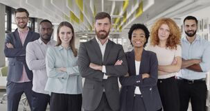 Positive multiracial company staff standing and crossing hands in office. Group of successful mixed workers with ther
