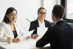 Positive hr executives laughing at job interview with successful. Positive multiracial hr team or friendly female executives laughing at funny joke during stock photography