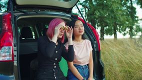 Women tourists looking through binoculars at view. Positive multiracial young women travelers sitting in car trunk, looking through binoculars at scenic view stock footage