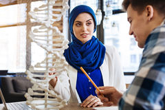 Positive muslim girl studying genetics with her groupmate. Interesting process. Pleasant smilign muslim girl sitting at the table with her groupmate and royalty free stock photos