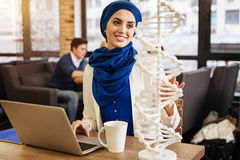 Positive muslim student learning genetics. New advancements in science. Cheerful beautiful muslim student sitting in the cafe and studying genetics while looking royalty free stock photography