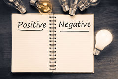 Positive Negative. Positive Versus Negative on notebook with glowing light bulbs Stock Image
