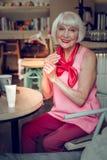 Positive nette Frau, die am Tisch sitzt stockfotografie