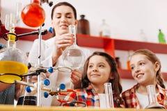Positive nette Mädchen, welche die Flasche betrachten Lizenzfreie Stockfotos
