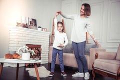 Positive nette Mutter und Tochter, die einen Tanz durchführt stockbild