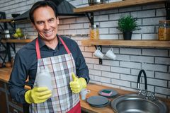 Positive nice adult man stand at sink in kitchen and pose on camera. He hold washing gel and smile. Guy show big thumb stock images