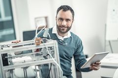 Positive nice adult man using 3d technology. 3d printing machine. Positive nice man using 3d technology while working as an engineer royalty free stock photography