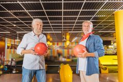 Positive nice aged men holding bowling balls. Bowling players. Positive nice men holding balls while playing bowling together stock images