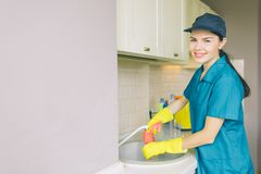 Positive and nice cleaner stands at sink and looks on camera. She washes water tube. Girl is cleaning in kitchen from royalty free stock photography