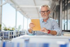 Positive nice elderly man reading the menu royalty free stock photo