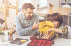 Positive nice father and son playing chess. In the middle of the game. Positive nice intelligent father and son sitting opposite each other and playing chess stock photo