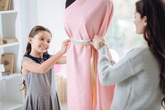 Positive nice girl working together with her mom. Interesting job. Positive nice delighted girl smiling and looking at the dress while working together with her Royalty Free Stock Photo