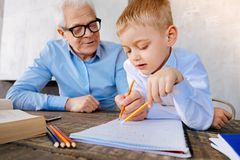 Positive nice grandfather helping his grandson. Time for studying. Positive nice smart grandfather sitting at the desk and helping his grandson with studying Royalty Free Stock Photos