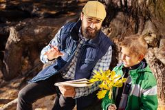 Positive nice man explaining to his son about nature. New discoveries. Positive nice men explaining his to his son about nature while being with him in the stock photography