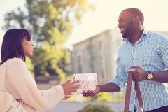 Positive nice man giving a present to his girlfriend Royalty Free Stock Images