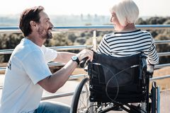 Positive nice man helping a disabled woman. Social duty. Positive cheerful nice men smiling and looking at the disabled women while helping her Royalty Free Stock Photos