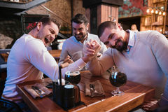 Positive nice men deciding who is stronger. Showing strength. Positive nice delighted men sitting at the table and armwrestling while deciding who is stronger stock images