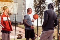 Positive nice men preparing for the game. Ready to play. Positive nice men standing together on the basketball court while preparing for the game royalty free stock images