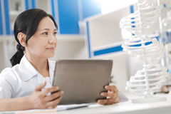 Positive nice scientist studying genome. Human body. Positive nice smart scientist looking at the gene model and holding a tablet while studying genome stock photo