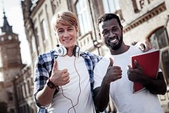 Positive nice student feeling happy. Absolutely satisfied. Positive nice joyful students standing together and showing OK gestures while feeling happy about Stock Photography