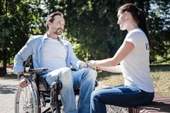 Positive nice woman looking at the disabled man. Sympathy and support. Positive nice young women looking at the disabled men and holding his hand while showing Royalty Free Stock Photos