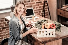 Positive nice woman sitting in front of the box with vegetables. Healthy food. Positive delighted nice woman sitting in front of the box with vegetables and Royalty Free Stock Images