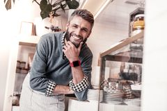 Positive nice young man touching his beard royalty free stock photo