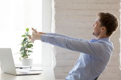Worker doing effective stretching exercises during the working day. Positive office worker distracted from work doing effective stretching exercises during the stock photography