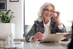 Positive Old Business Woman Is Signing Papers Stock Photo