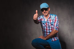 Positive old casual man in trucker hat making  ok sign Stock Photos