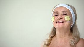 Positive old lady applying cucumber face mask, optimistic attitude to age royalty free stock images