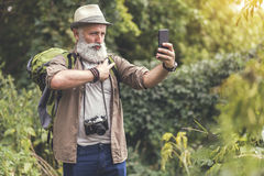 Positive old man photographing himself on cellphone Stock Photos