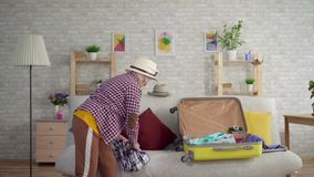 Positive old woman packing her suitcase for travel. Positive old woman in the hat packing her suitcase for travel preparing for vacation stock video