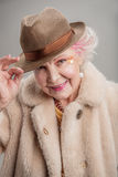 Positive old woman holding her hat by hand royalty free stock photos