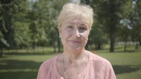 Portrait old grey-haired woman looking at camera standing in summer park. Leisure outdoors. Mature caucasian lady. Positive old woman in pink dress looking at stock video