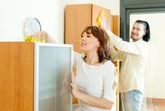 Positive Paare, die den Staub von den Möbeln abwischen Lizenzfreies Stockfoto