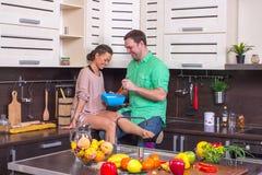 Positive Paare, die Freude bei der Stellung im k kochen und zeigen Lizenzfreie Stockfotos